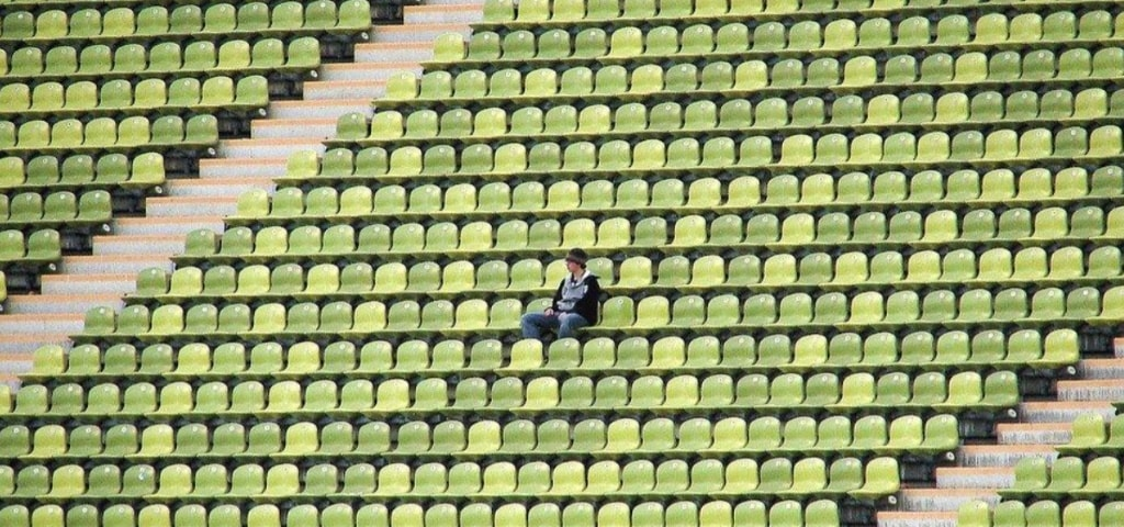 A lonely fan sits in the stands
